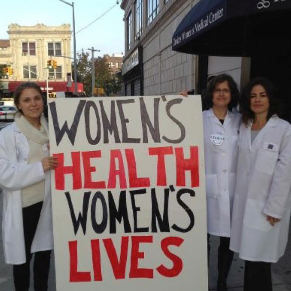 Volunteers hold sign outside Choices stating Women's Health Women's Lives